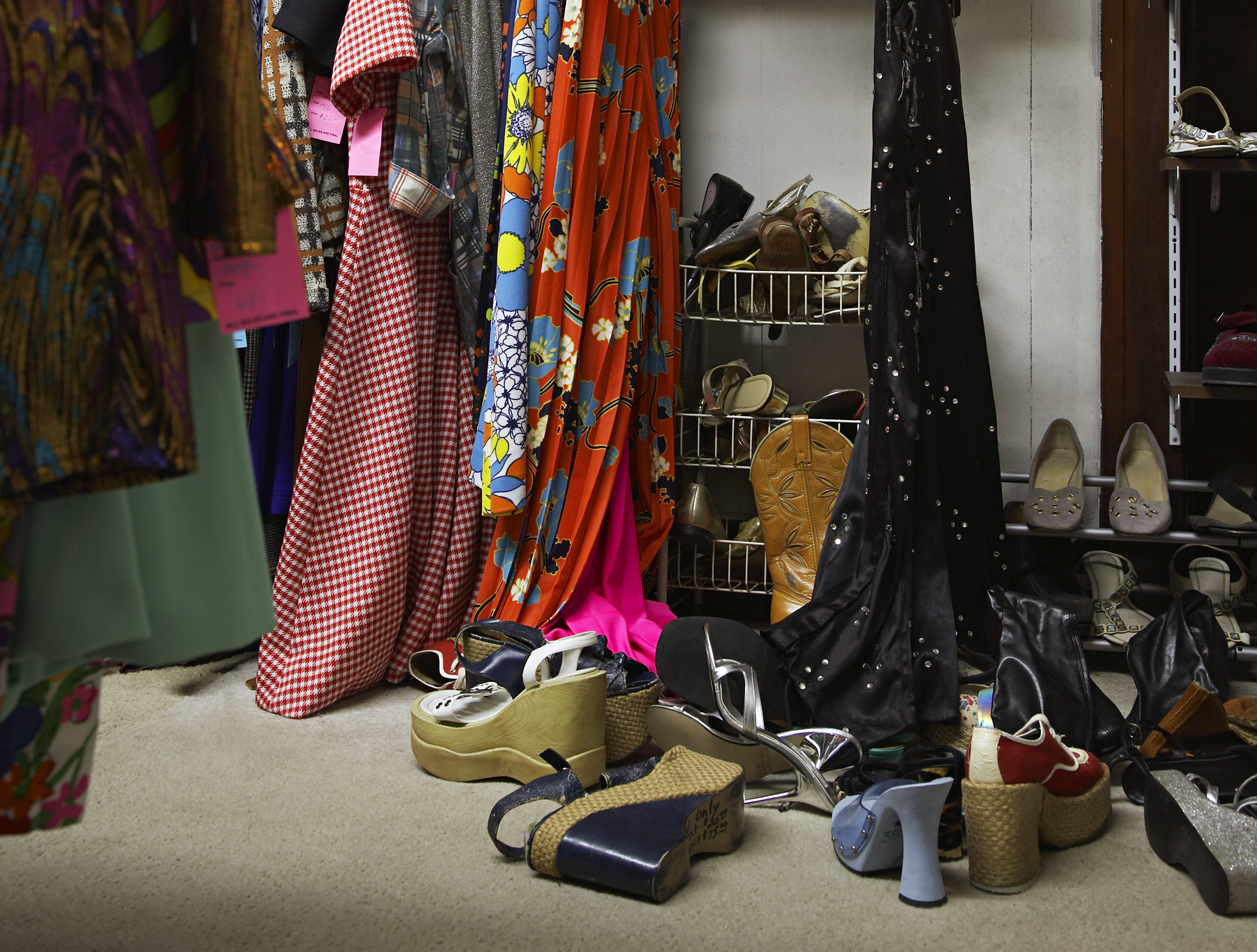 Crowded clothing racks and piled shoes in thrift store