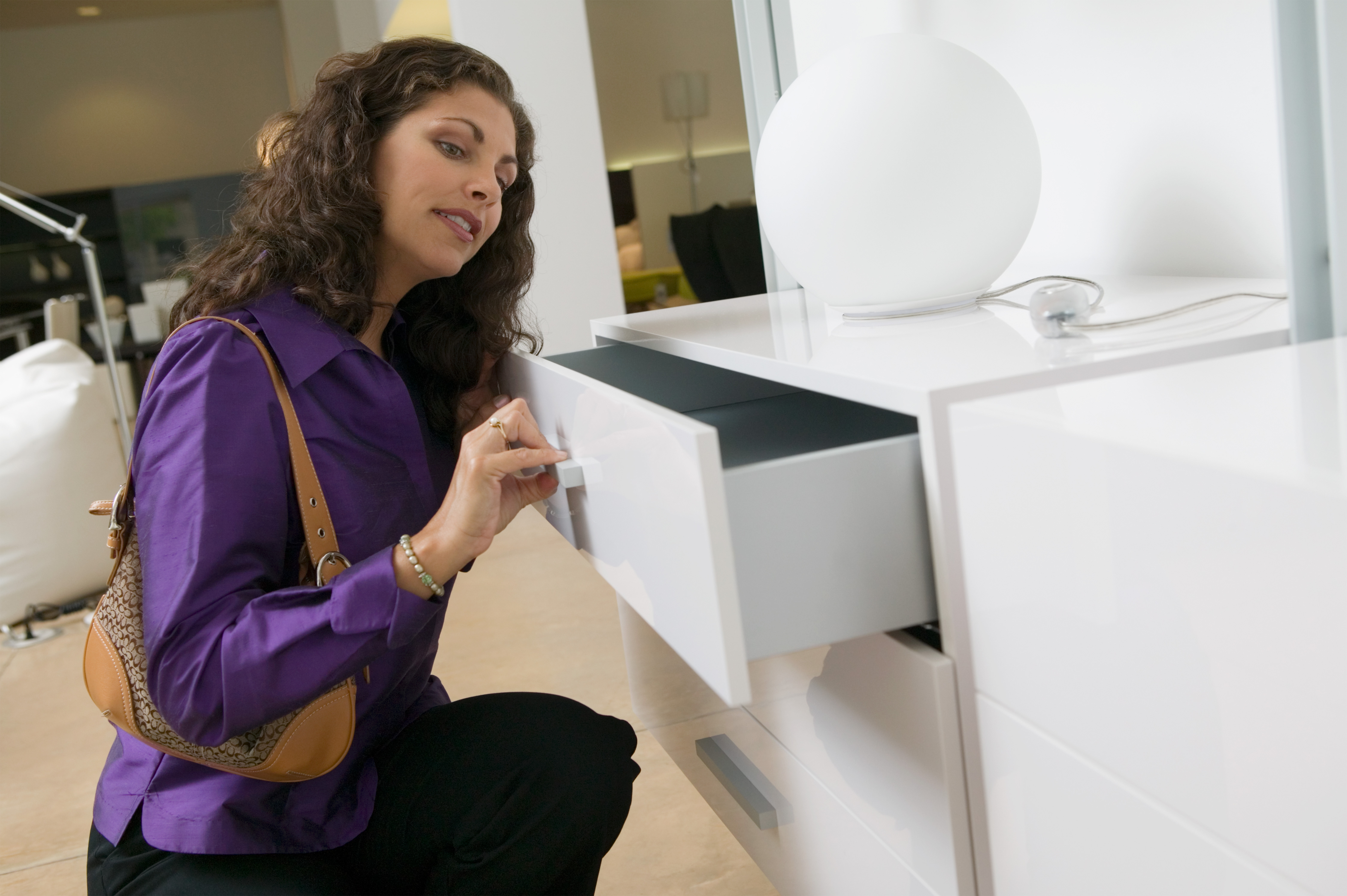 Woman examining white dresser drawer in furniture store close up