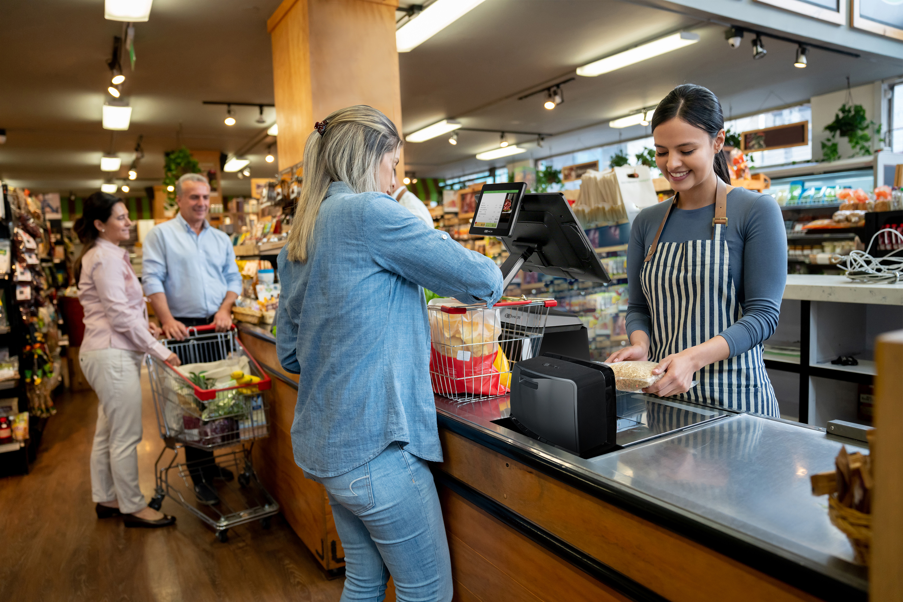 Cheerful employee at supermarket checking out customers