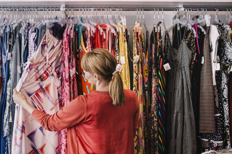 Woman looking at tops in a clothing store