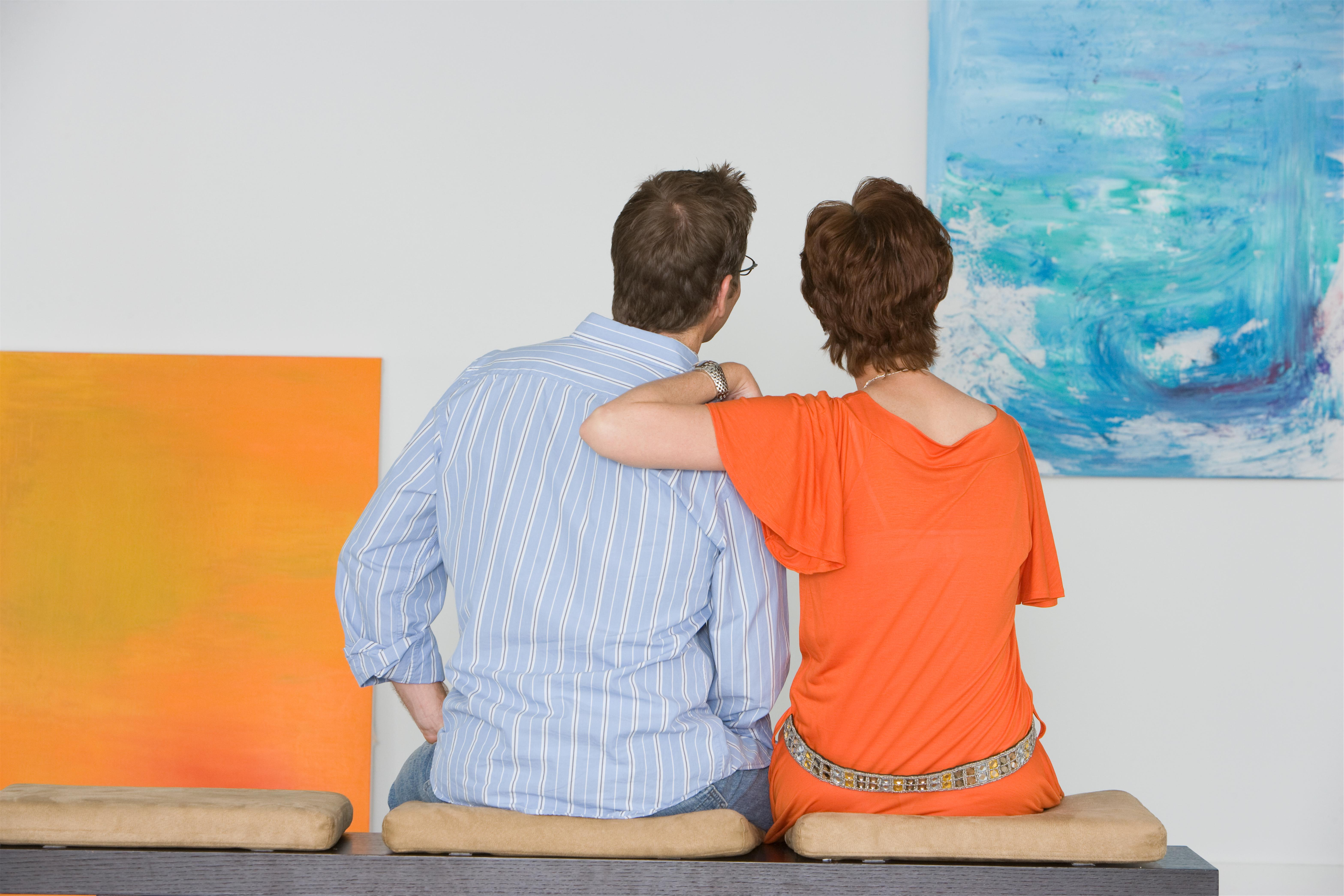 Couple contemplating paintings in gallery 2