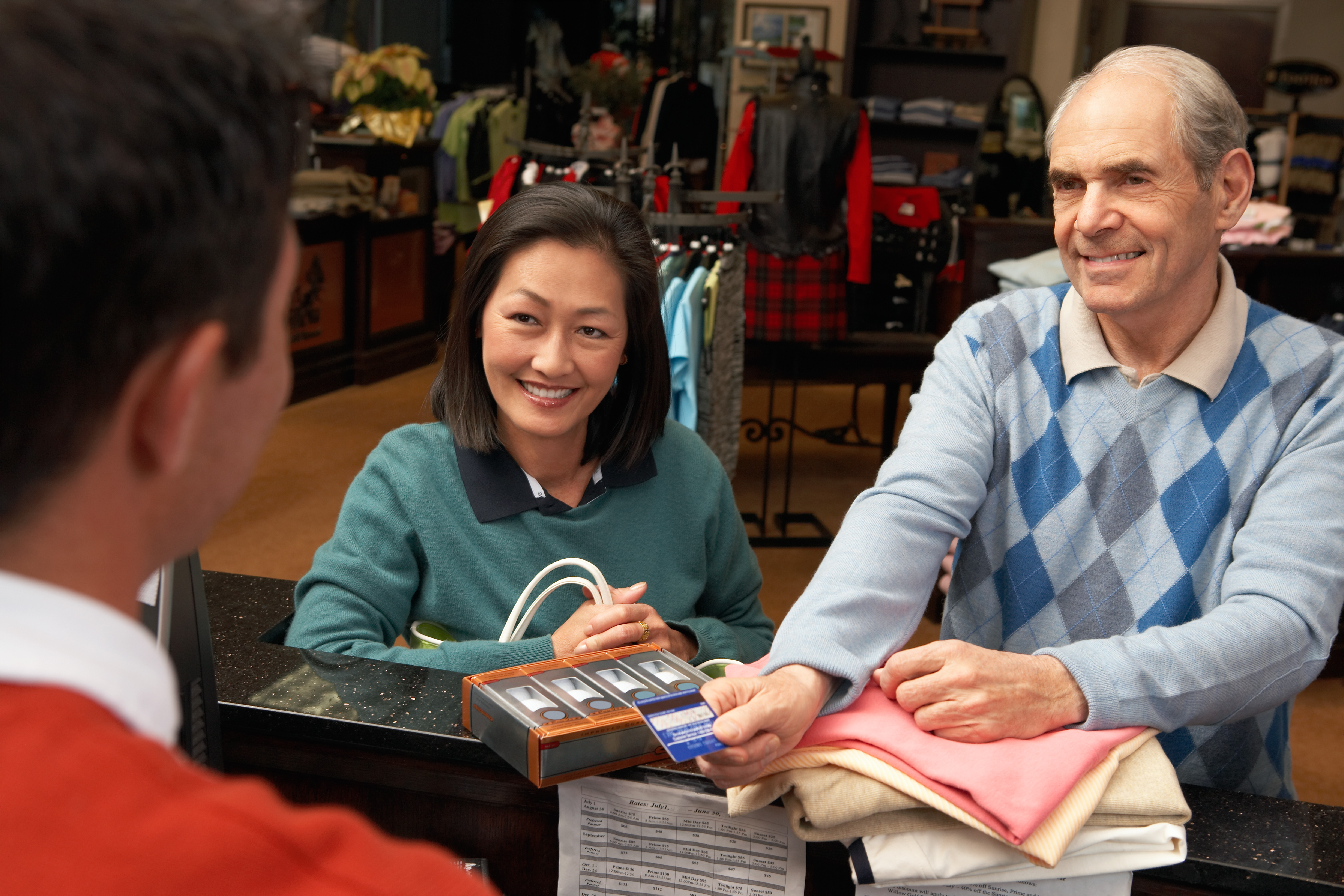 Couple paying for golf apparel in golf store by credit card at checkout counter