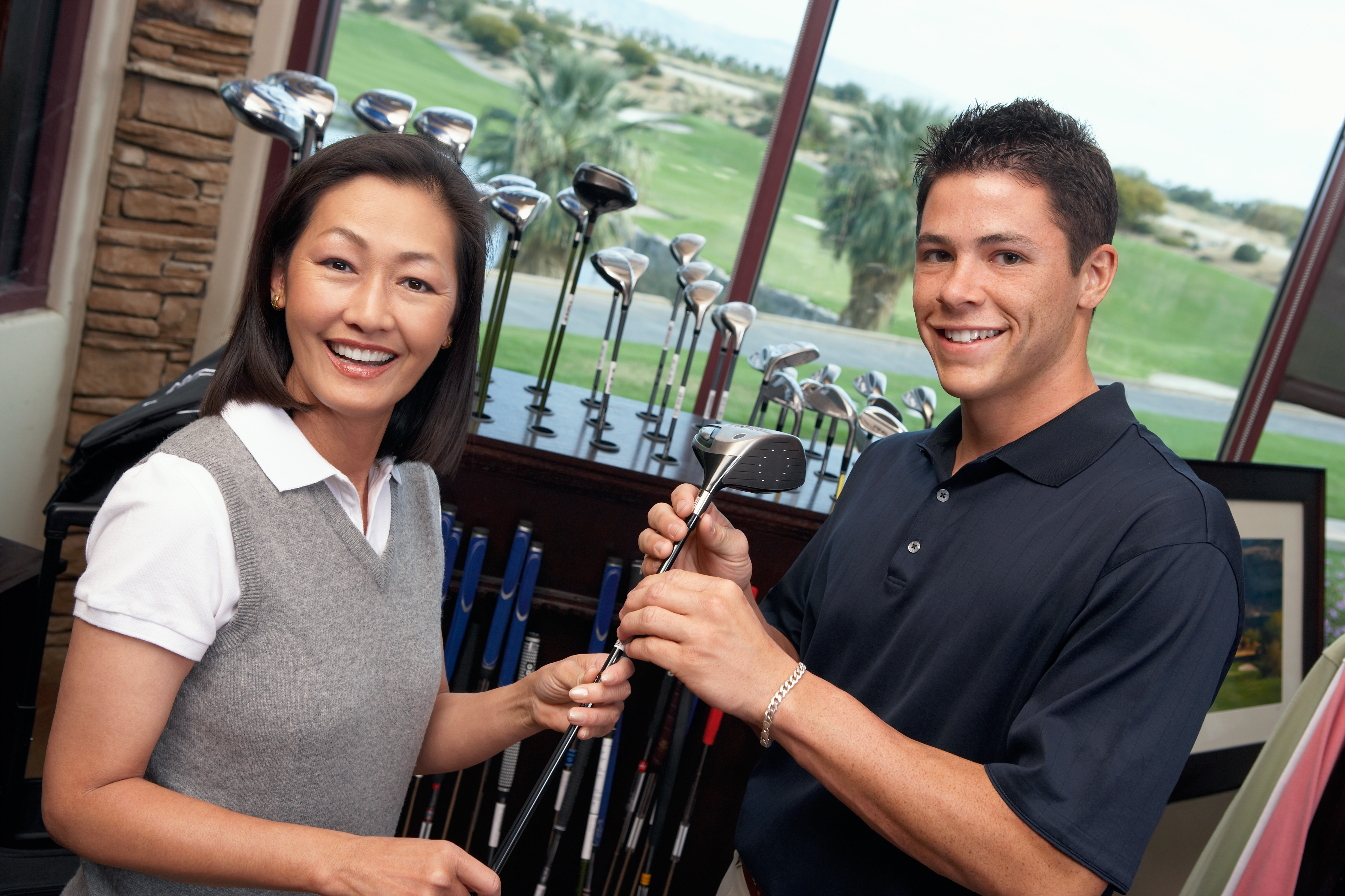 Smiling clerk assisting mid adult woman shopping for golf clubs in golf shop